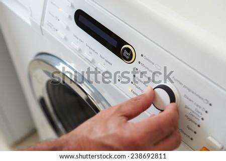 Close Up Of Man Choosing Cycle Program On Washing Machine - stock photo