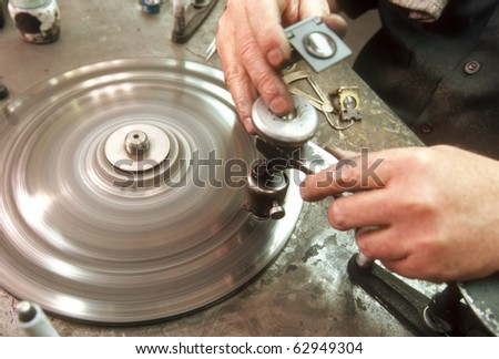 close-up of man cutting diamond facets on spinning wheel - stock photo