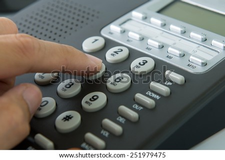 Close up of man dialing on a landline telephone - stock photo