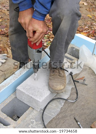 Close-up of man drilling hole in concrete cap block - stock photo