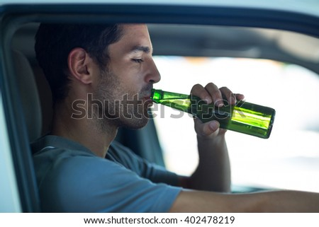 Close-up of man drinking alcohol while sitting in car - stock photo