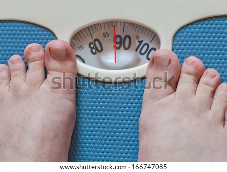 Close-up of man feet weighing in bathroom  - stock photo