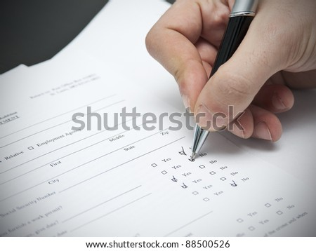 close-up of man filling a resume with a pen - stock photo