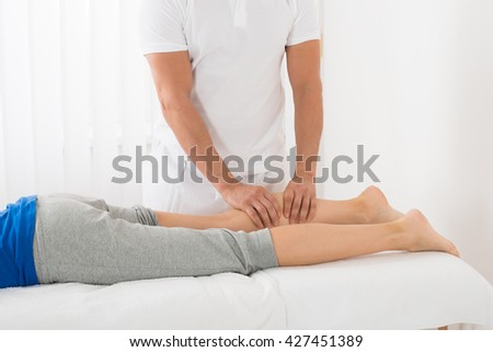 Close-up Of Man Giving Leg Massage To Woman In Spa