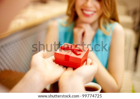 Close-up of man giving red giftbox to happy girl - stock photo