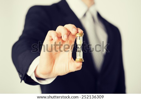 close up of man hand holding hourglass. - stock photo