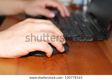 Close-up of man hand on mouse while working on laptop - stock photo