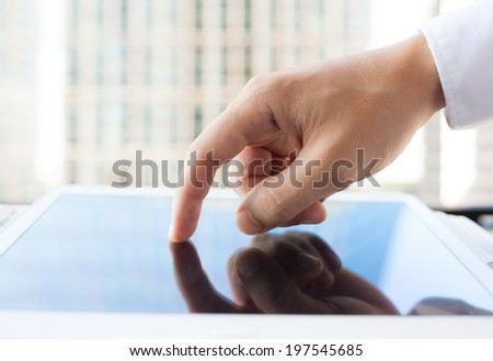 Close up of man hand touching digital tablet. - stock photo