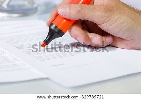 Close-up of man hand with highlighter over document, checking the content before signing. Concept of business and agreement - stock photo