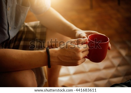 close up of man hands holding red cup of coffee - stock photo