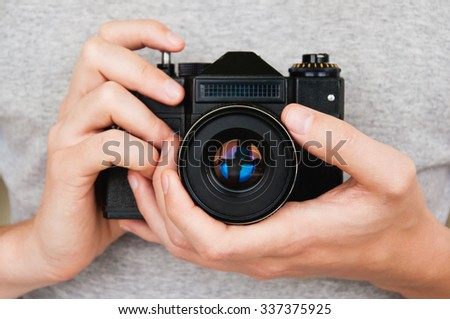 Close up of man hands holding retro camera - stock photo