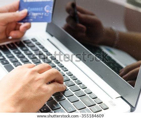 Close-up of man hands with laptop/PC and credit card as online shopping or online payment concept. Selective and shallow focus. - stock photo