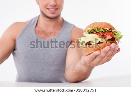 Close up of man holding a hamburger and showing it to camera. He is sitting at the table and smiling. Focus on a burger. Isolated on background - stock photo