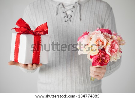 close up of man holding bouquet of flowers and gift box. - stock photo