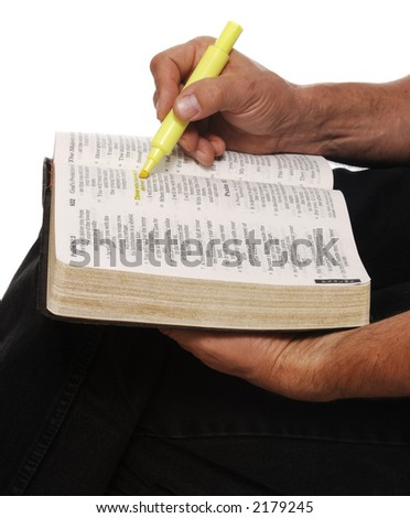 close-up of man holding open Bible on knee, hi-lighting verses
