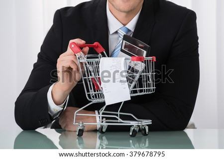 Close-up Of Man Holding Shopping Trolley With Receipt And Calculator - stock photo