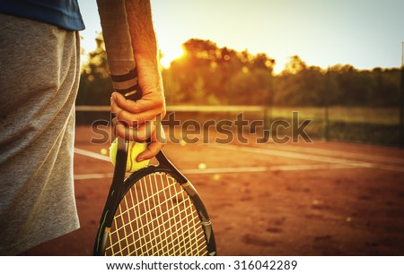 Close up of man holding tennis racket on clay court. In his hand is tennis ball. On court is sunset./Man holding tennis racket - stock photo