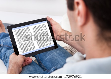 Close-up Of Man Holding Touch Screen Device Showing An E-book - stock photo