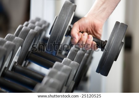 close up of man holding weight in gym - stock photo