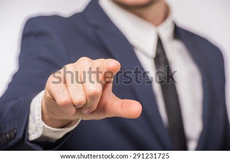 Close-up of man in suit pointing with finger on white background. Business success concept. - stock photo