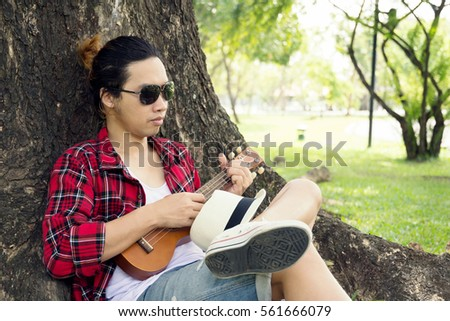 Close up of man is relaxing in public park with his Ukulele.
