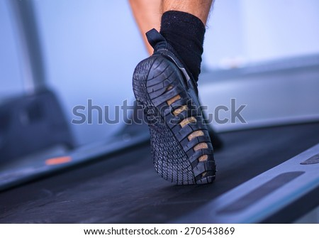Close-up of man legs in sneakers on treadmill  - stock photo