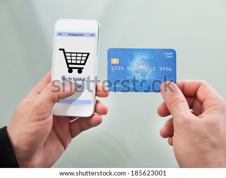 Close-up Of Man Paying With Credit Card On Mobile Phone - stock photo
