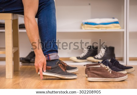 Close-up of man putting on shoes in dressing room. - stock photo