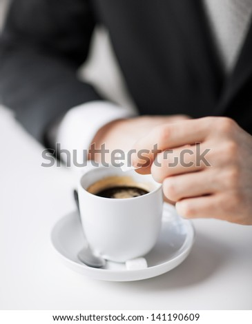 close up of man putting sugar into coffee - stock photo