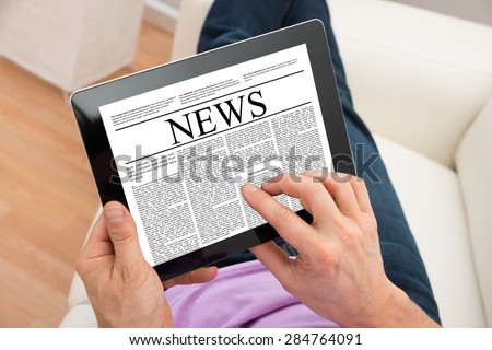 Close-up Of Man Reading News On Digital Tablet At Home - stock photo