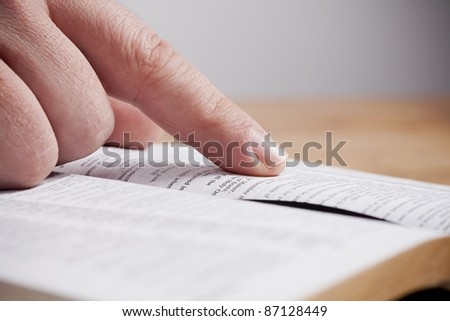 Close up of man reading through the Bible. - stock photo