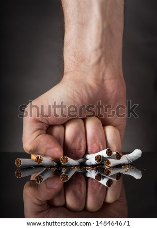 Close-up Of  Man's Fist Crushing Cigarettes Over Black Background - stock photo