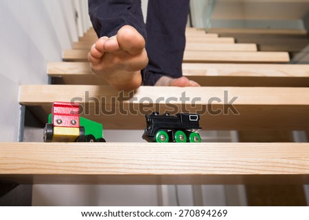 Close-up of man's foot and toys left on steps - stock photo