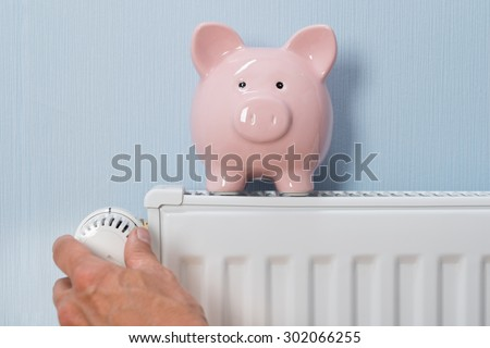 Close-up Of Man's Hand Adjusting Thermostat With Piggy Bank On Radiator - stock photo