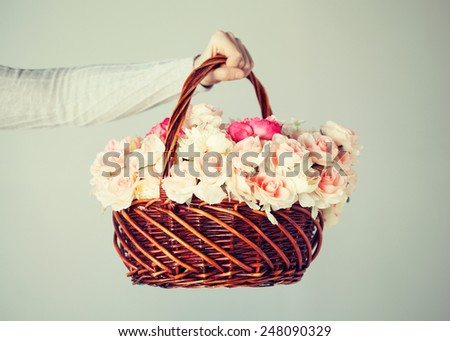 close up of man's hand holding basket full of flowers. - stock photo
