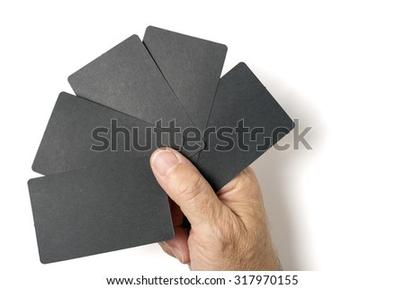 Close up of man's hand holding five blank black card. Studio shot isolated on white. - stock photo