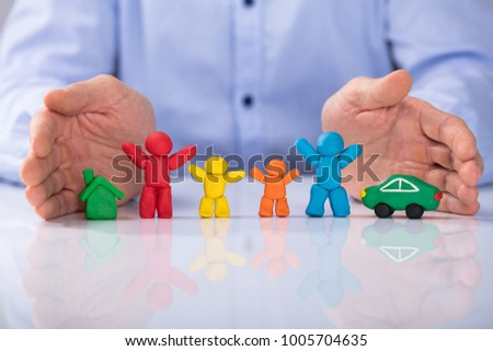 Close-up Of Man's Hand Protecting The House, Car And Colorful Family Made Up Of Clay