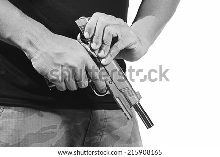 Close up of man's hand reloading gun, Man hold and loading ammunition his pistol on white background. Army, Semi-automatic handgun, 45 pistol, Black&White.