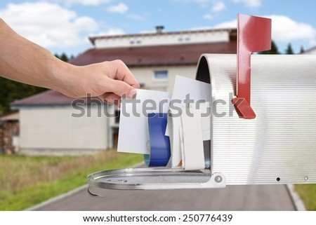 Close-up Of Man's Hand Taking Letter From Mailbox Outside House - stock photo