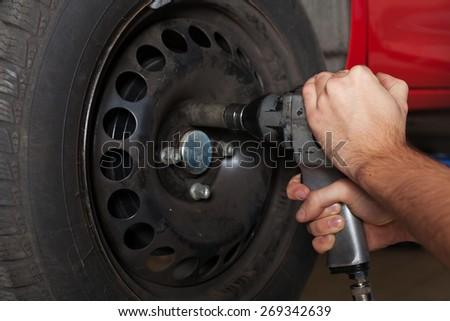 Close up of man's hands changing wheel. - stock photo