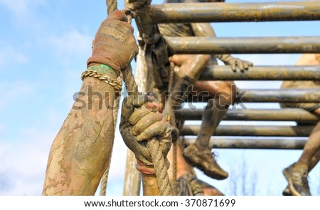 Close-up of man's hands climbing the rope. Other sportsmen ob background. Unrecognizable - stock photo