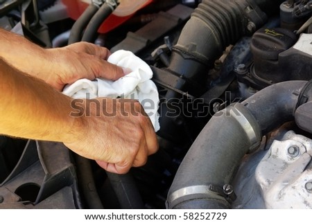 close-up of man's hands holding a piece of cloth checking the engine of a car - stock photo