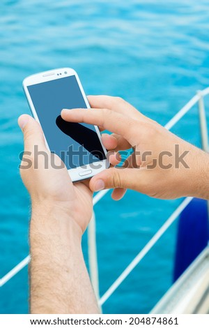 Close-up of man's hands using smartphone while sailing - stock photo