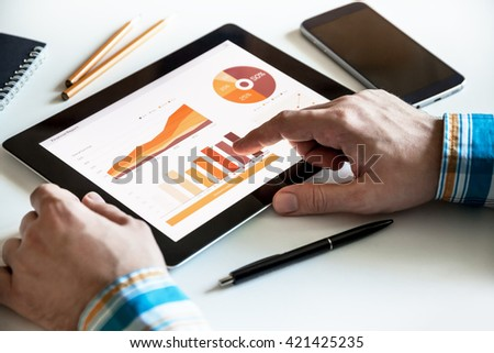 Close up of Man's hands working with digital tablet, Financial Graph charts on screen - stock photo