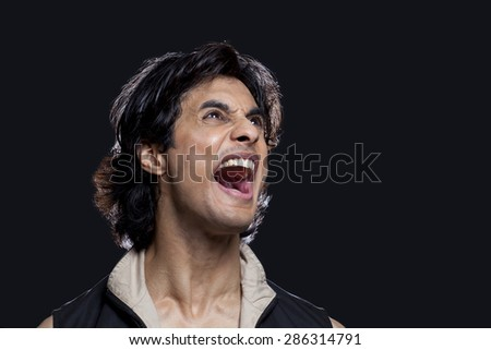 Close-up of man shouting while looking up against black background