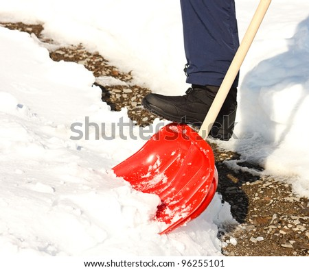 Close-up of man shoveling snow with red shovel.Cleaned path in background. - stock photo