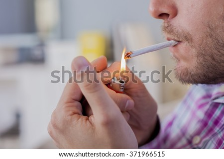 Close up of Man smoking cigarette. Man lighting the cigarette. - stock photo