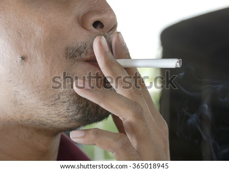 Close up of man smoking cigarette selective focus - stock photo