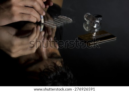 Close-up of man snorting drugs through rolled up banknote - stock photo