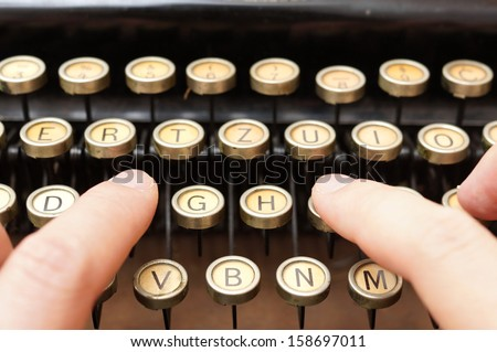 close up of man typing with old typewriter - stock photo
